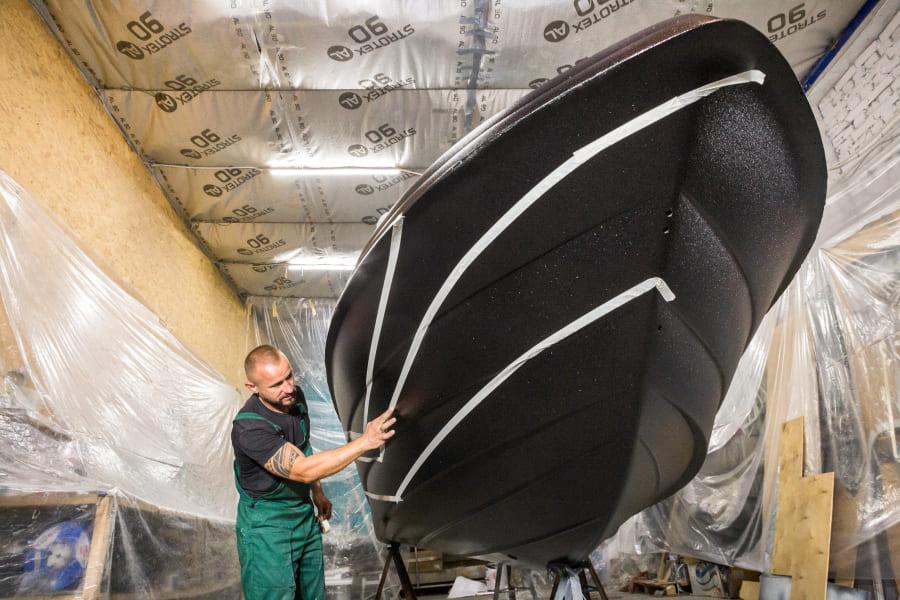 Николай Волков проверяет, высохла ли краска на корпусе катера