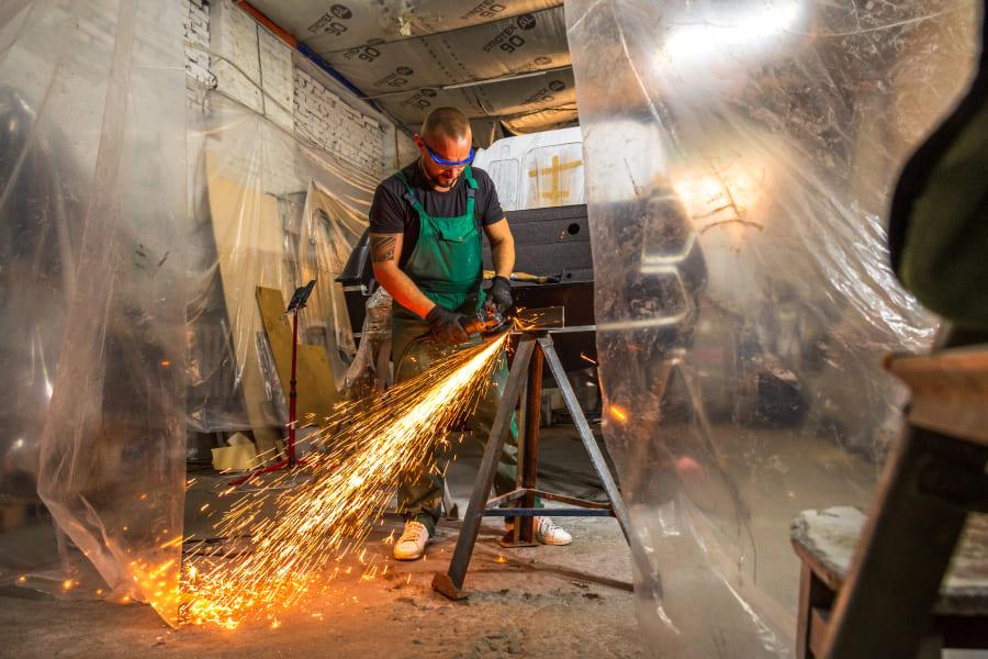 Николай срезает болгаркой острые углы металлического стапеля